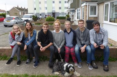 Rich House Poor House Ep 1 - The Caddys ordinarily live in a huge townhouse in an affluent part of Bristol. In this photo, they are sat outside their temporary home for our week-long experiment: a comparatively tiny council house in Weston-super-Mare. Letty, Iszzy, Charlie, Claire, Flo, George, James. Dog: Buddy.