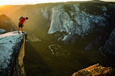 Honnold peers over the edge of Taft Point, across the Yosemite Valley from the granite escarpment known as El Capitan.